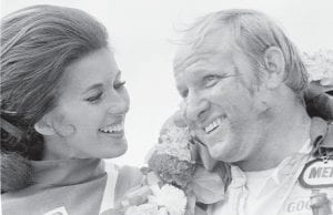 """— Union Oil (Unical) """"Race Stopper"""" Ann Romeo, left, made eyes at Cale Yarborough of Timmonsville, S.C., winner of the first Motor State 500 at Cambridge Junction, Michigan on June 16, 1969. He was driving a 1969 Mercury and swept up $17,625 in prize money with a time of 3 hours, 35 minutes and 28 seconds. Yarborough went on to compete 560 races in his career, which ended in retirement in 1988. Romeo was one of the original Race Stopper """"trophy girls."""" (AP Photo)"""