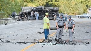 Kentucky State Police troopers examine debris left behind following a fatal crash on KY 15 near Isom. KSP Trooper Scott Caudill said the preliminary investigation into the crash indicated a Chevrolet pickup truck driven by 20-year-old Ethan Adams of Whitesburg was traveling southbound when his vehicle crossed the center line and collided nearly head-on with a northbound coal truck, which then overturned. Adams died at the scene. KY 15 was closed for about seven hours following the crash. (Photo by Chris Anderson)