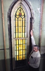 """MCHC CEO L.M. """"Mike"""" Caudill demonstrates the length of a stained glass window uncovered in a building that sits on the lot formerly occupied by the First Baptist Church of Whitesburg. (Photo by Ben Gish)"""