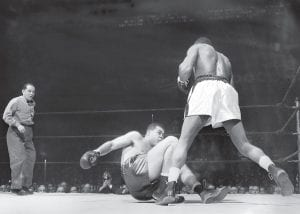 Heavyweight boxing match was big news here Challenger Jersey Joe Walcott stands over heavyweight champion Joe Louis after knocking the champion down for a count of seven in the fourth round of their scheduled 15-round title fight at Madison Square Garden in New York. Walcott also knocked down Louis for a count of two in the first round. Louis won the December 5, 1947 fight in a controversial split decision. Detailed coverage of the fight, including a full recap, appeared in the December 12, 1947 edition of The Mountain Eagle. (AP Photo)