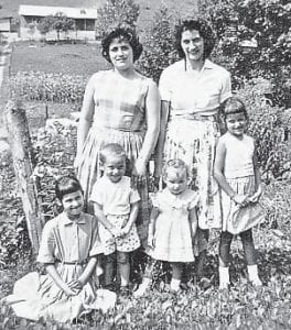This photograph of Della Howard Pennington, Dorothy Pennington Tacket, Charlene Tacket Mason, David Pennington, Delores Tacket Holbrook, and I, Jeanette, Yonts, was taken at the head of Stinking Branch. In the background you can see the home of Chester and Margie Pennington Adams.