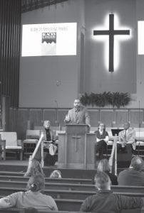 William Isom II speaks at the Martin Luther King Jr. Breakfast in Whitesburg last week as Carol Ison, Nell Fields, and Bishop Willie Lamb look on from behind the pulpit. (Photo by Sam Adams)