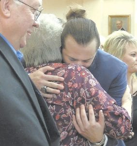 Stabbing victim Christopher Puckett hugged Connie Hogg, the mother of murder victim Michael Hogg, after the sentencing hearing for James R. Huffman IV. Looking on at left is Don Hogg, father of Michael Hogg.