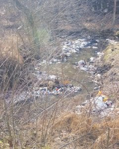 This portion of Millstone Creek was left full of garbage Tuesday after an 18-wheeler hauling garbage from the Letcher County Transfer Station overturned and spilled its load. Cleanup workers were on the scene shortly after the accident. (Photo by Sam Adams)
