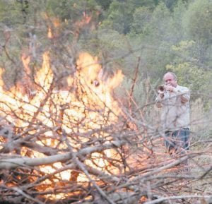 Ellis Keyes played a trumpet as the sun set on a bonfire as it was being lit on his property at Love's Branch near Colson last fall. Photographers and reporters visited Keyes's property while persons associated with white nationalist groups were staying there. Letcher Commonwealth's Attorney Edison G. Banks II has filed court action asking that Keyes be declared ineligible to run for the office Banks now holds. (Photo by Tod Seelie, The Village Voice)