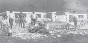 "The foundation for the new high school was laid prior to 1914. The United States needed skilled workers, so they sent notices out to other countries. Italy had a lot of men without work, so some of them decided to come to the U.S. and some of them settled in Whitesburg. They mined ""blue stone"" out of a quarry next to the school hill and cut and laid it by hand to form the foundation on which the school was built. The gentleman lying down in the center of the picture is Frank Majority, Sr. and seated next to him is his brother, Vincent Mongiardo. Vincent kept the family's original spelling and is the grandfather of Daniel Mongiardo of Hazard. Frank Majority, Jr. of Whitesburg used his father's shortened spelling of his name."