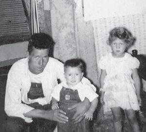 Eli Stidham sits with his children, Emory and Altonia