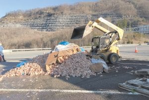 A small loader gathers up raw chickens along U.S. 23 on Sunday after a wreck at Jenkins. Jenkins Police Officer Jim Stephens said a truck carrying the chickens overturned as it attempted to negotiate the sharp turn onto U.S. 119 toward Whitesburg from U.S. 23. Stephens said the truck was hauling about 20 tons of refrigerated chicken down Pine Mountain when it overturned. The payload had to be offloaded before the truck could be righted and the scene cleared. The driver of the truck was not injured. Stephens said speed was likely a factor. The intersection has been the site of numerous tractor-trailer wrecks. (Photo by Chris Anderson)