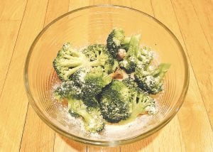 This photo shows broccoli with a dusting of Parmesan cheese and roasted garlic. (AP photo)