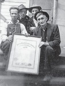 Henry Calvin Pennington and Dewey Brown display a United Mine Workers of America document with Willie King and Russell Howard.