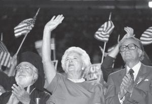 In this Aug. 18, 1988, file photo, Barbara Bush cheers and waves to her husband, George H.W. Bush, as Rev. Billy Graham, right, stands beside her at the Republican National Convention in New Orleans. Mrs. Bush died Tuesday at the age of 92. (AP Photo/Tannen Maury)