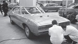 "Pontiac became known for its muscle cars like the 1968 GTO shown in this photo taken September 14, 1967. (AP Photo) When GM shut down Pontiac brand On April 27, 2009, the struggling American auto giant General Motors (GM) says it plans to discontinue production of its more than 80-year-old Pontiac brand. Pontiac's origins date back to the Oakland Motor Car, which was founded in 1907 in Pontiac, Michigan, by Edward Murphy, a horse-drawn carriage manufacturer. In 1909, Oakland became part of General Motors, a conglomerate formed the previous year by another former buggy company executive, William Durant. The first Pontiac model made its debut as part of the Oakland line in the 1920s. The car, which featured a six-cylinder engine, proved so popular that the Oakland name was eventually dropped and Pontiac became its own GM division by the early 1930s. Pontiac was initially known for making sedans; however, by the 1960s it had gained acclaim for its fast, sporty ""muscle cars,"" including the GTO, the Firebird and the Trans Am. The GTO, which was developed by auto industry maverick John DeLorean, was named after a Ferarri coupe, the Gran Turismo Omologato. According to The New York Times: ""More than any other G.M. brand, Pontiac stood for performance, speed and sex appeal."" Pontiacs were featured in such movies as 1977's ""Smokey and the Bandit,"" in which actor Burt Reynolds drove a black Pontiac Trans Am, and the 1980s hit TV show ""Knight Rider,"" which starred a Pontiac Trans Am as KITT, a talking car with artificial intelligence, alongside David Hasselhoff as crime fighter Michael Knight. By the mid-1980s, Pontiac's sales reached their peak. Experts believe GM hurt the Pontiac brand in the 1970s and 1980s by opting for a money-saving strategy requiring Pontiacs to share platforms with cars from other divisions. — The History Channel"