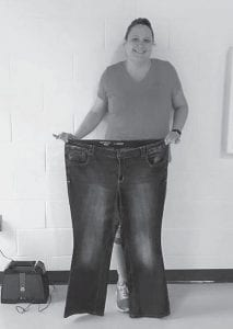 Shellie Elswick holds the jeans she wore before losing more than 100 pounds.