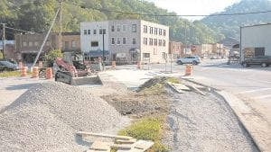NEW INTERSECTION UNDERWAY — Contractors for the Kentucky Highway Department were expected to finish concrete and paving work on a new intersection in downtown Whitesburg this week. Workers were moving two parking lot entrances at the intersection at the foot of College Hill, and installing a sidewalk. Striping and signage will finish the realignment. Some had promoted a roundabout for the location, but engineers said there is not enough room for a roundabout there. (Photo by Sam Adams)