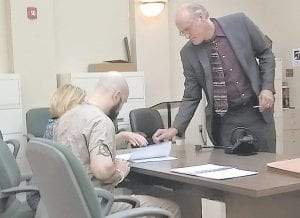 PLEADS GUILTY – Patrick Smith, accused in the New Years 2014 slaying of Michael Hogg in Whitesburg, pleaded guilty this week to facilitation to commit murder, and other charges. Pictured, Smith (seated) verifies his signatures on the plea agreement with his attorney, Tom Griffiths. (Photo by Sam Adams)