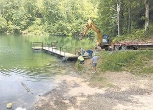 DOCKING STATION — Letcher County Soil Conservation District board member James McAuley stood in the water working on a new boat dock at Fishpond Lake at Payne Gap while Judge/Executive Jim Ward, County Dog Warden Dustin Hollin and others offered their assistance. (Photo by Chris Anderson)