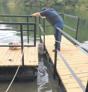 James McAuley is in the water working on a new boat dock at Fishpond Lake while Dustin Hollin assists.