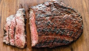 """This grilled flank steak with garlic herb sauce was prepared from a recipe in cookbook, """"Cooking At Home With Bridget And Julia."""" (Daniel J. van Ackere/America's Test Kitchen via AP)"""