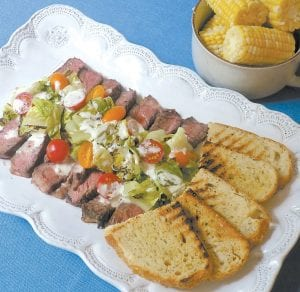 This photo shows a grilled steak salad, as prepared from a recipe by Sara Moulton. (Sara Moulton via AP)