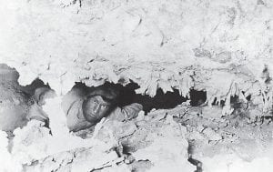 "This photograph, taken a short time before Floyd Collins's last venturesome journey through the mazes of Sand Cave in Cave City, Kentucky, on Feb. 9, 1925, shows Collins peering through a break in one of the interior partitions of the cavern. The original Associated Press caption said that for ""10 days this gritty and daring mid westerner whose hard luck has stirred world wide interest and sympathy has been pinioned in darkness, wetness and horror under a ten top boulder in the cold entrails of the earth. Neither pains nor expense are being spared to take him living or to retrieve him dead. Rescuers are toiling like sons of Anak to reach him quickly."" (AP Photo)"