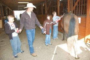 Drew Baldwin (second from left) handed Zach Bates (far left) a brush while Amber Holbrook and Logan Wynn groom a horse.