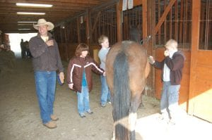 Drew Baldwin (far left) laughed as Zach Bates (far right) held  shirt over his nose because he thought the horse smelled bad. Also pictured are Amber Holbrook and Logan Wynn.