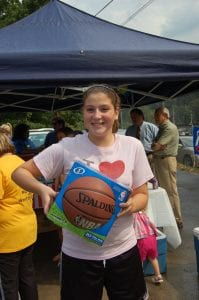 Alexis Cornett posed for a photograph after she received a basketball from members of the Whitesburg Rotary Club.