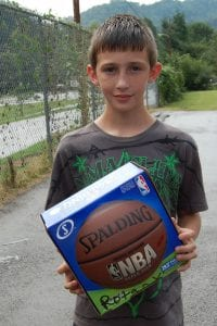 Chase Adams was one of several children who received new basketballs recently from the Whitesburg Rotary Club.