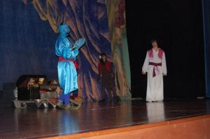 Genie, played by Robbie Rowlette, explained to Abu the monkey, played by Nick Madden, and Aladdin, played by Paul Sokolowich that he can grant Aladdin three wishes.