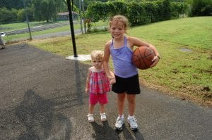 Sisters Morgan and Madison Hurst took a break from playing basketball to pose for a photograph.