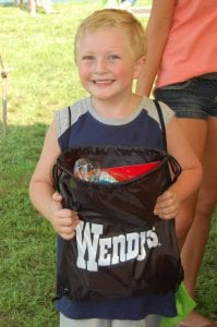 Jackson Adams, 6, of Cowan, smiled when he received his free school supplies at the Letcher County Kids' Day Back to School Bash at River Park in Whitesburg on July 29. His mother, Angel Adams, stood behind him.