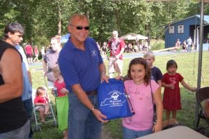 Paul Leon Adams, president of Whitaker Bank, handed 10-year-old Salena Gibson her free school supplies at the Letcher County Kids' Day Back to School Bash at River Park in Whitesburg on July 29. Salena, whose father is Danny Gibson, is a fourth-grade student at Cowan Elementary School.