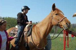 Debbie Champion helped Zach Bates as he climbed onto a horse.