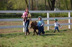 Leah Baldiwn (far left) carried her daughter, Anna Belle, as she walked a horse with Mark Howard. Her son Boone followed closely behind.